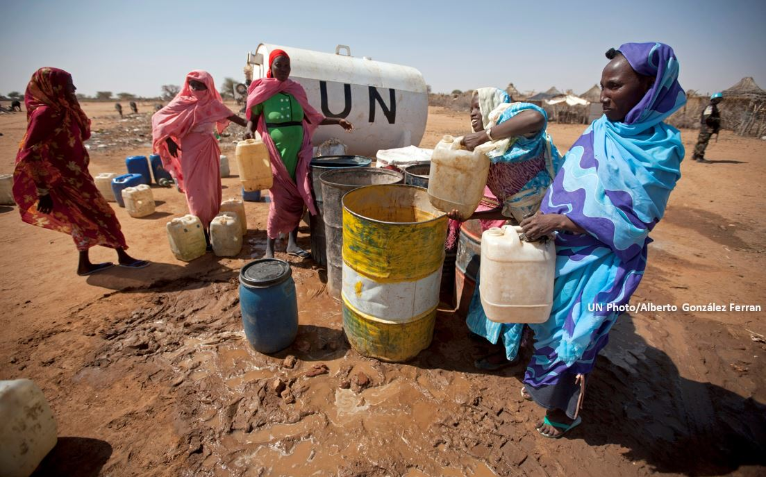 Women who were displaced after fleeing violence in their native Darfur villages collect water from a tank installed by UNAMID Sudan